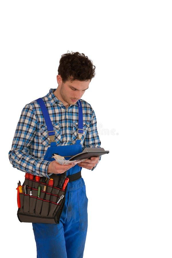 Jeunes artisan/artisan avec une ceinture d'outil, l'argent et un calcul d'isolement sur le fond blanc photos stock