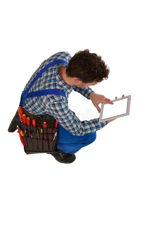 Jeunes artisan/artisan avec une ceinture et un comprimé d'outil d'isolement sur le fond blanc photo stock