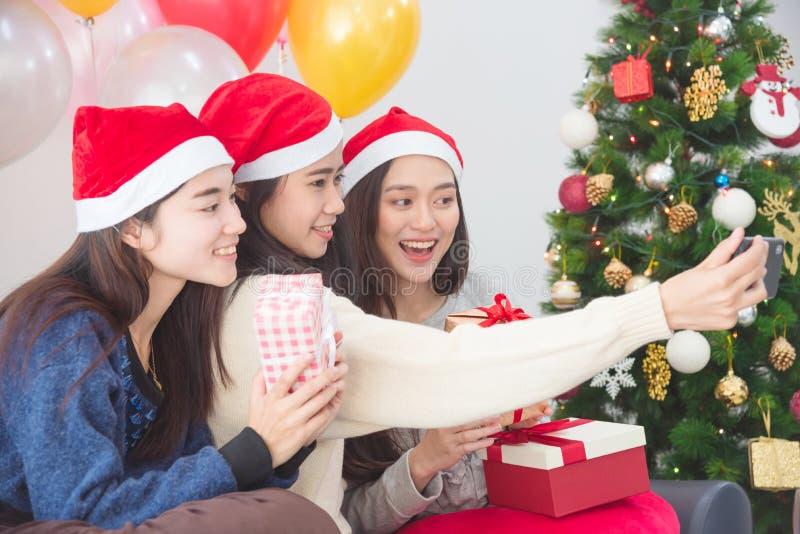 Jeunes asiatiques prenant la photo par le téléphone portable à la fête de Noël images libres de droits