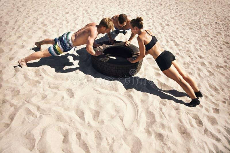Jeunes athlètes faisant des pousées sur le pneu images libres de droits