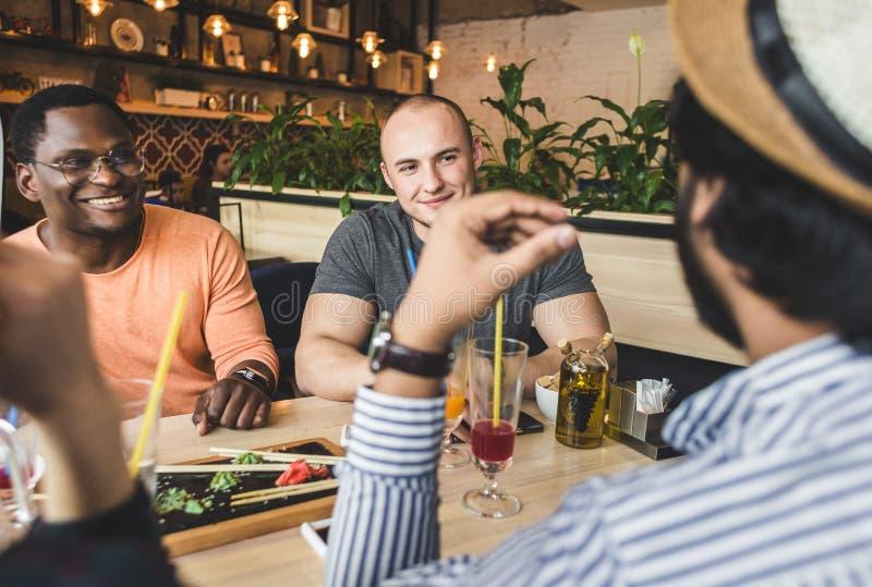 Jeunes attirants de rassemblement dans le caf? Les amis causent, ont l'amusement, cocktails de boissons et mangent image libre de droits