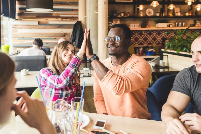 Jeunes attirants de rassemblement dans le caf? Les amis causent, ont l'amusement, cocktails de boissons et mangent photo stock