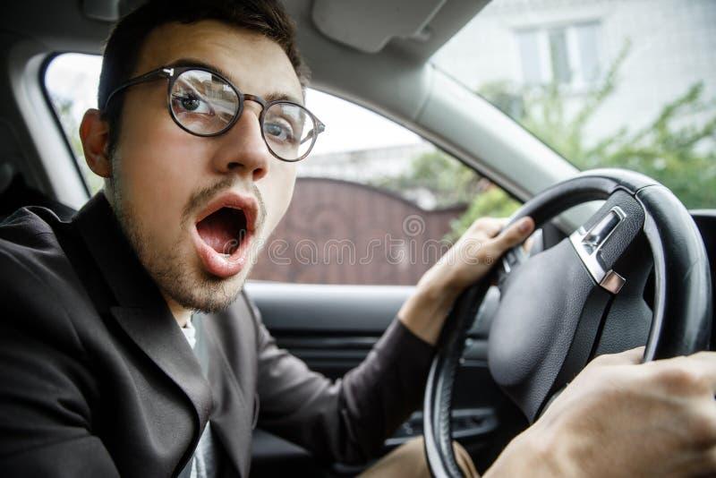 Jeunes bâillements de type tout en regardant la caméra Il s'assied à sa voiture Ses mains sont sur le volant photographie stock