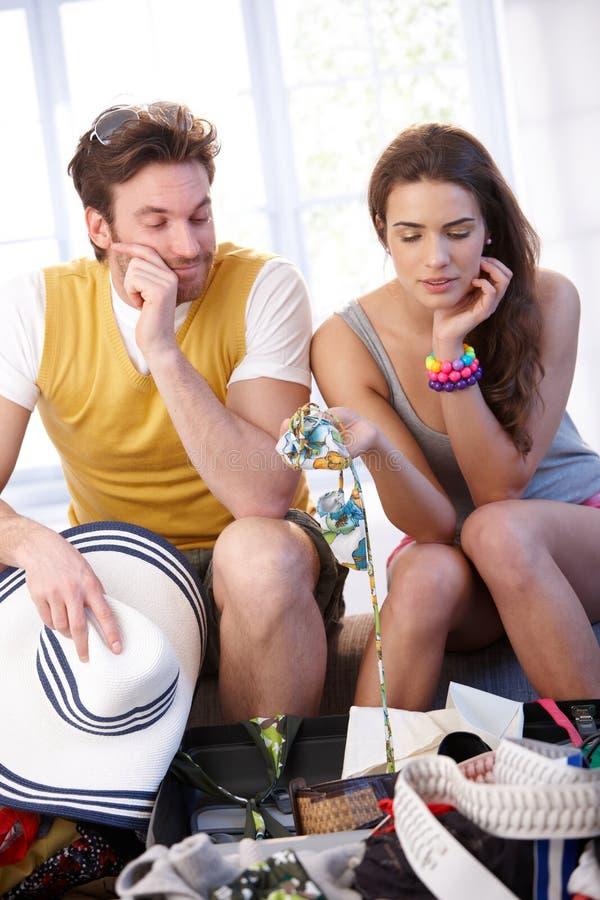 Jeunes bagages d'emballage de couples pour la course de vacances photo stock