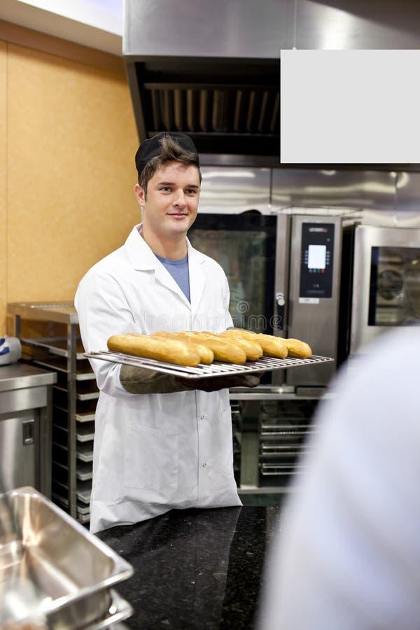 Jeunes baguettes et pains de fixation de boulanger images libres de droits