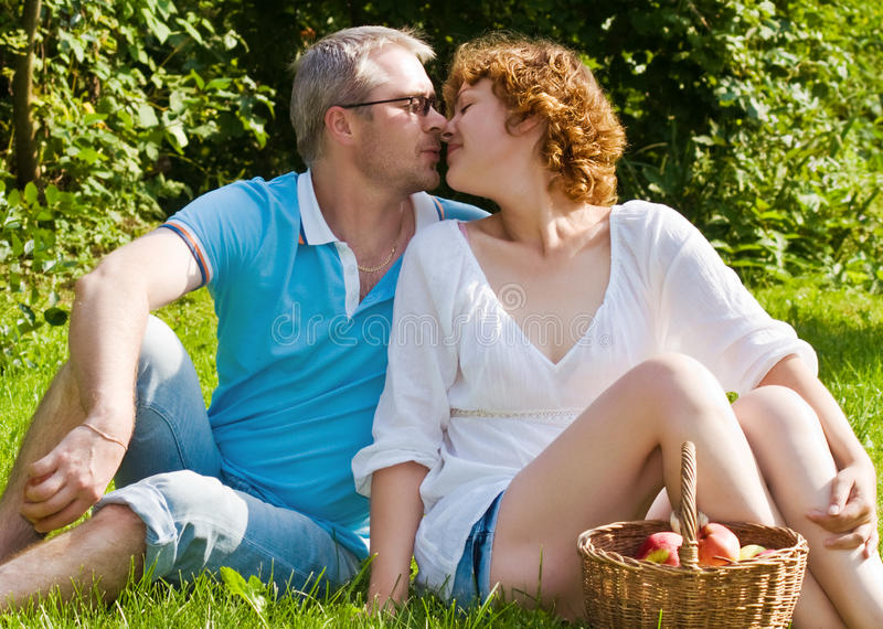 Jeunes baisers de paires, se reposant sur une herbe photographie stock