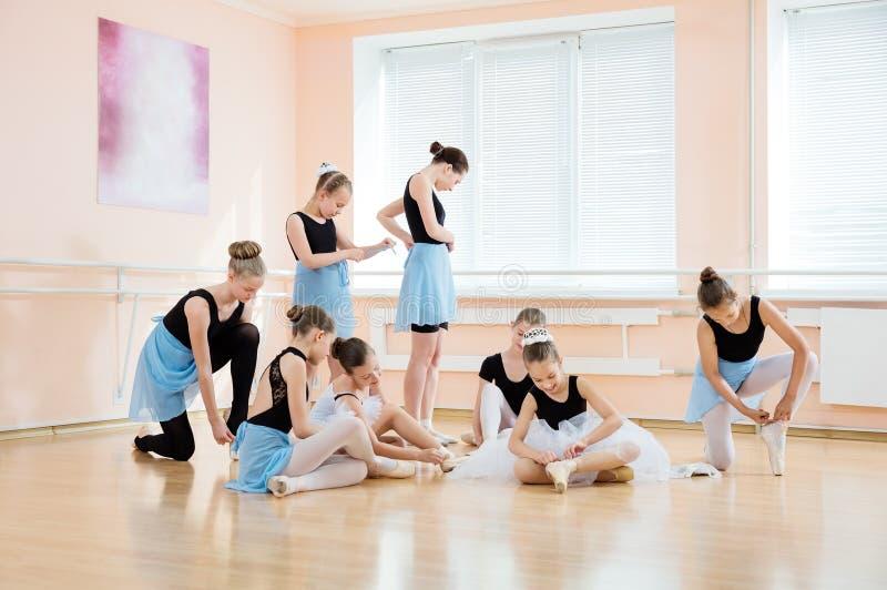 Jeunes ballerines mettant sur des chaussures de pointe et ajustant des costumes photo stock