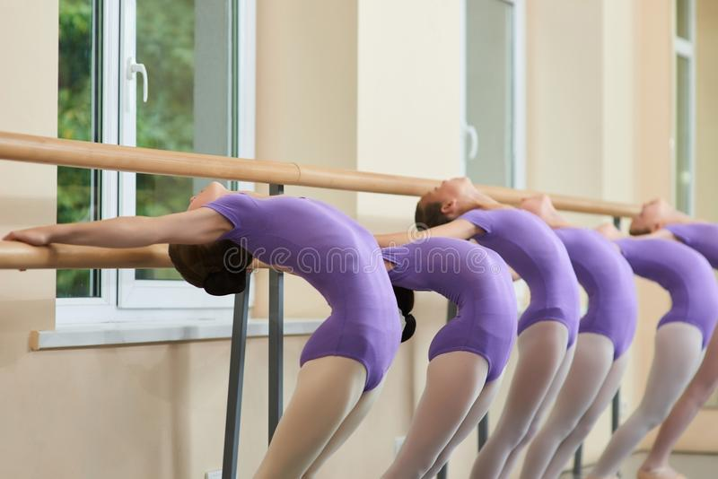 Jeunes ballerines s'étirant au barre de ballet photos libres de droits
