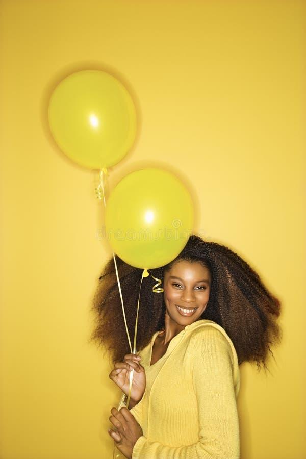 Jeunes ballons afro-américains de fixation de femme. images stock