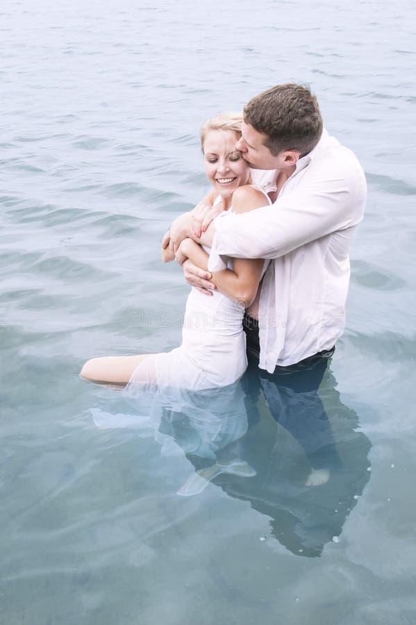 Jeunes beaux amants dans la piscine de l'eau partageant un moment intime photo libre de droits
