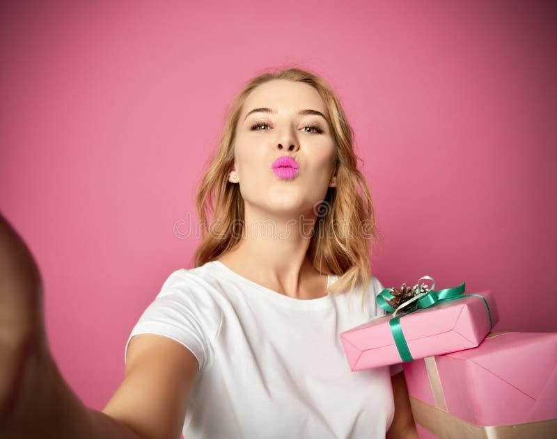 Jeunes beaux cadeaux de cadeau de Noël de prise de femme souriant et faire la photo de selfie avec son mobile de téléphone portab images libres de droits