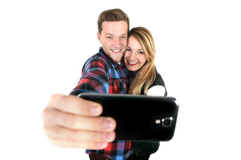 Jeunes beaux couples américains dans l'amour prenant la photo romantique de selfie d'autoportrait ainsi que le téléphone portable image stock