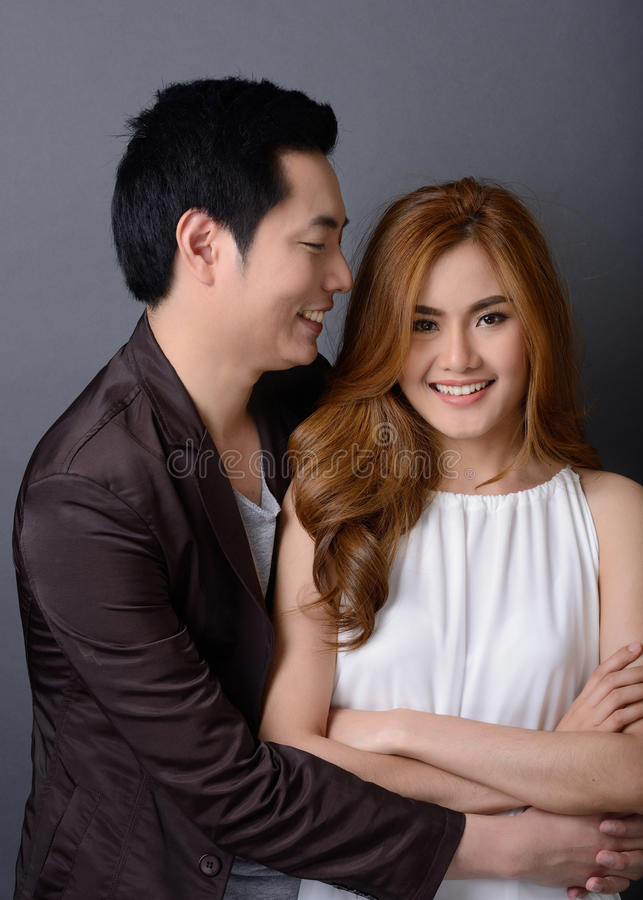 Jeunes beaux couples asiatiques posant et souriant dans le studio pour le pre-w images stock