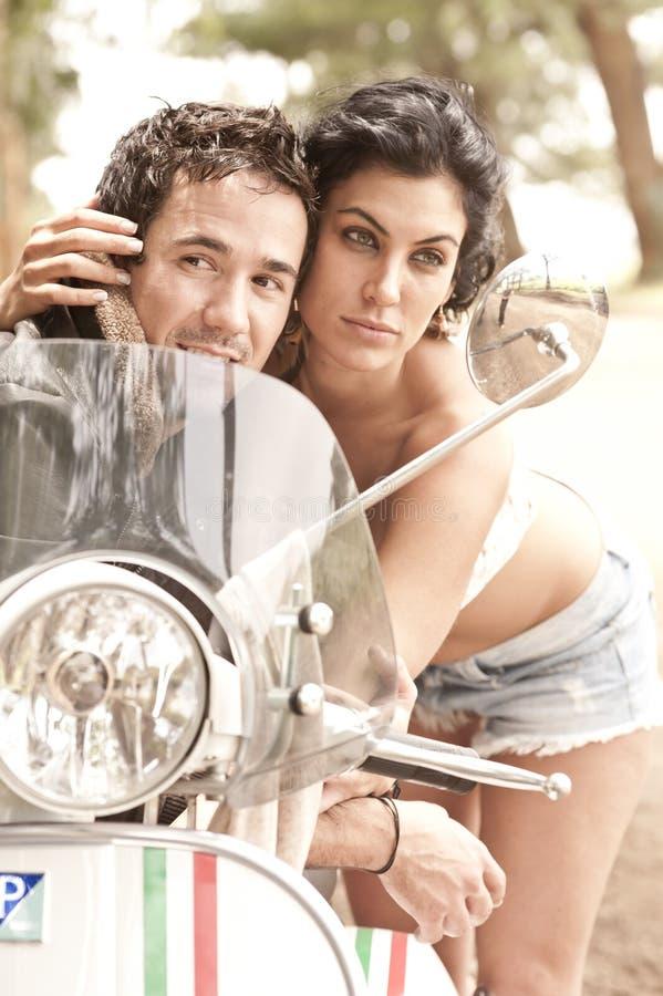 Jeunes beaux couples ayant l'amusement avec le scooter photographie stock libre de droits