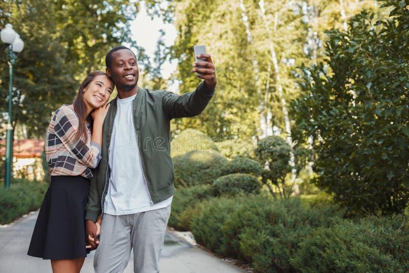 Jeunes beaux couples faisant le selfie au parc photo stock
