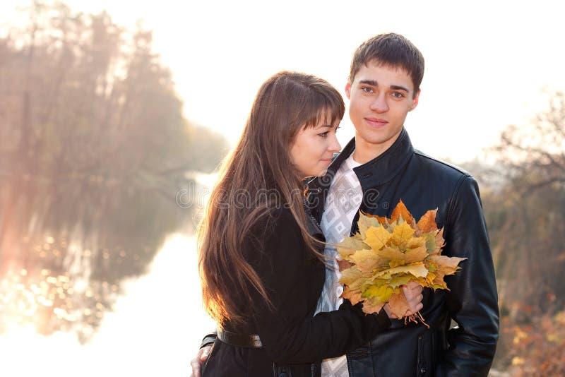Jeunes beaux couples heureux dans l'amour éclairé à contre-jour photos stock