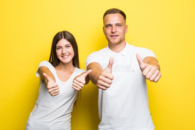 Jeunes beaux couples heureux montrant des pouces et regardant la caméra au-dessus du backgroun jaune photos stock