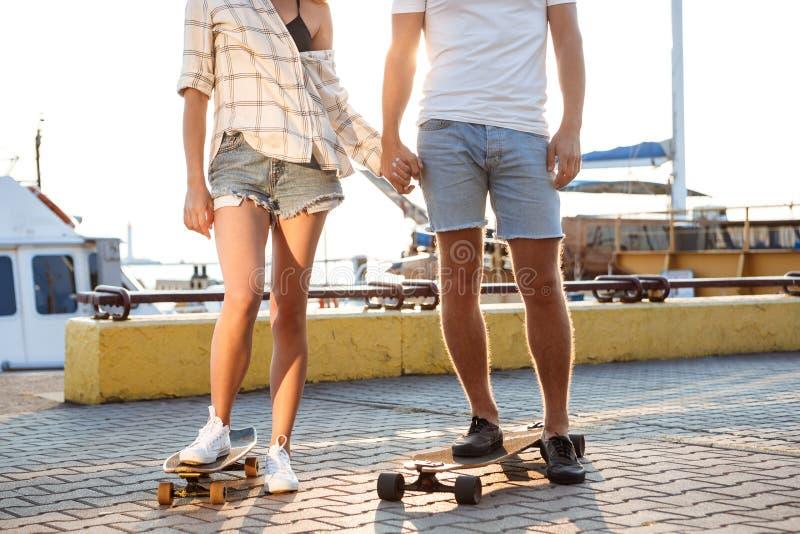 Jeunes beaux couples marchant au bord de la mer, faisant de la planche à roulettes Fermez-vous des jambes photos stock
