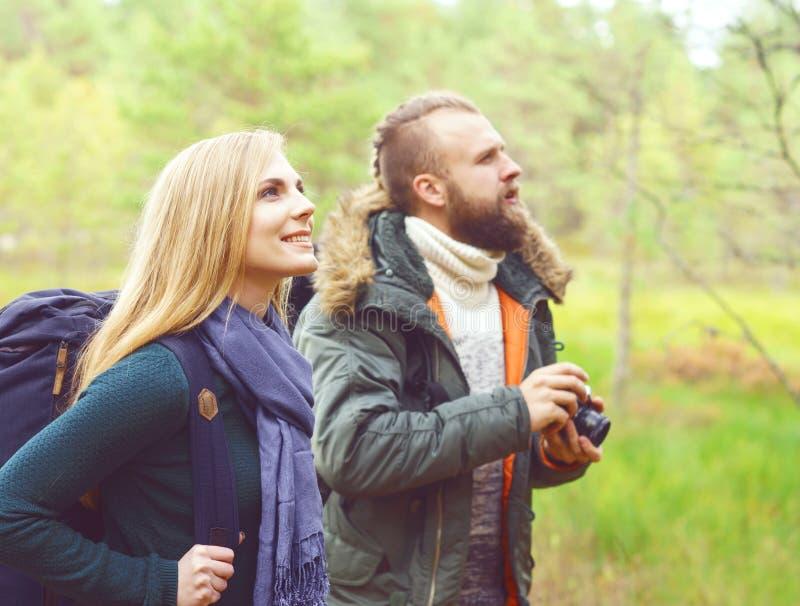 Jeunes beaux couples marchant dans la forêt et prenant des photos Ca photos libres de droits