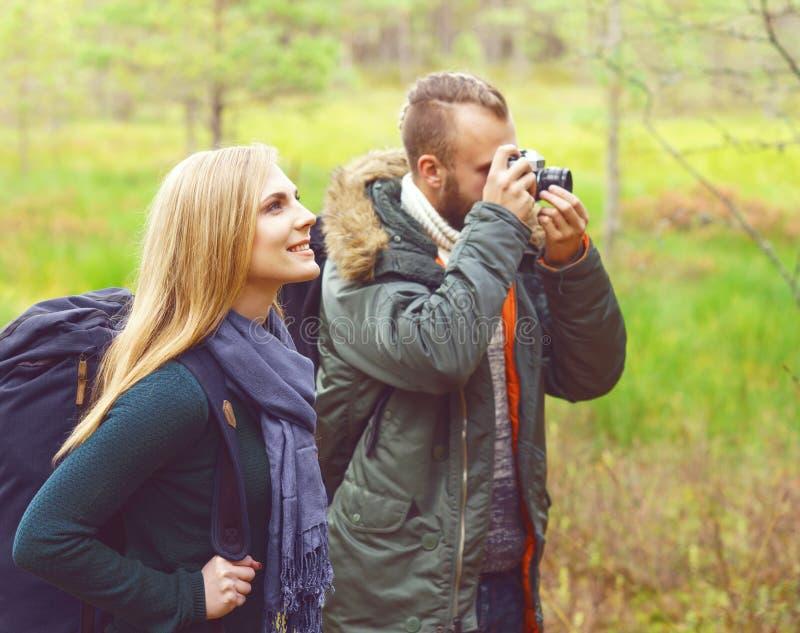 Jeunes beaux couples marchant dans la forêt et prenant des photos Ca image libre de droits