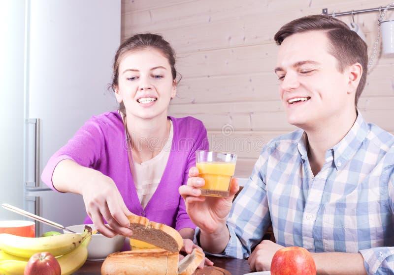 Jeunes beaux couples prenant le petit déjeuner à la table photos stock