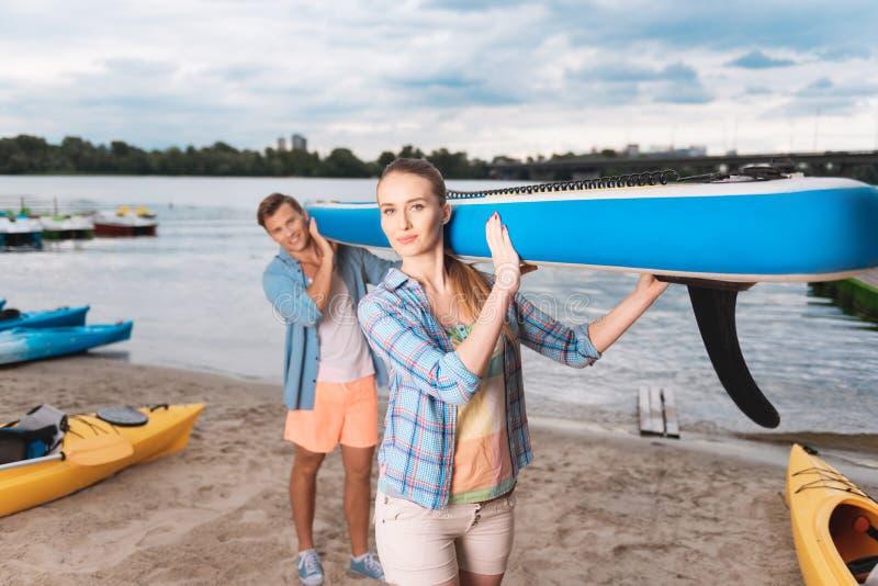 Jeunes beaux couples tenant le bateau bleu se préparant au tour de rivière photos stock