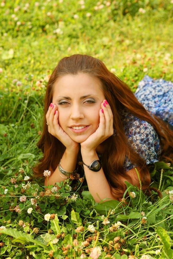 Jeunes belles configurations de fille sur une herbe photos libres de droits