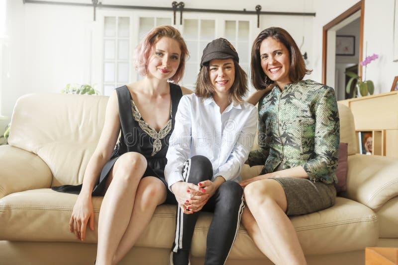 Jeunes belles dames sur le sofa en cuir image stock