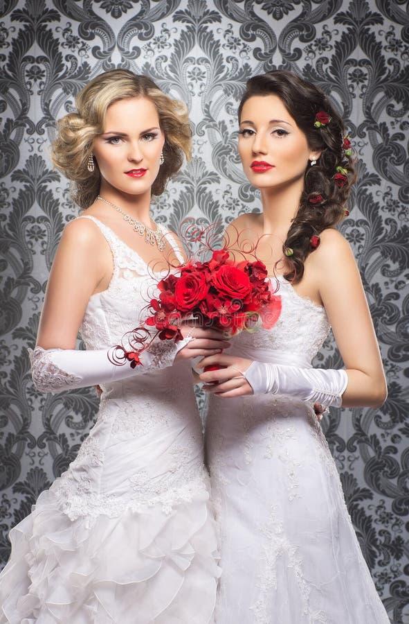 Jeunes, belles et émotives jeunes mariées avec de belles fleurs images stock