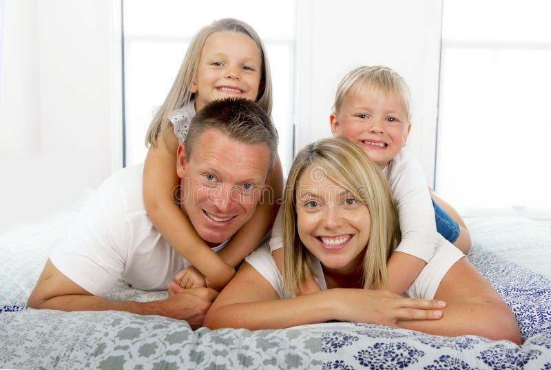Jeunes belles et rayonnantes années de mensonge doux de pose heureux de sourire des couples 30 à 40 sur le lit avec le petit fils photographie stock