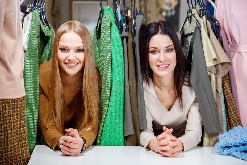 Jeunes belles femmes au magasin de tissu Meilleurs amis partageant le temps gratuit ayant l'amusement et faisant des emplettes au photographie stock libre de droits