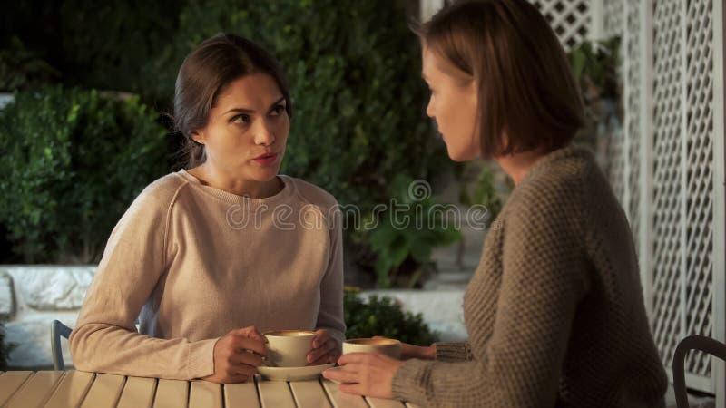 Jeunes belles femmes parlant, café potable sur la terrasse, relations d'amitié photographie stock