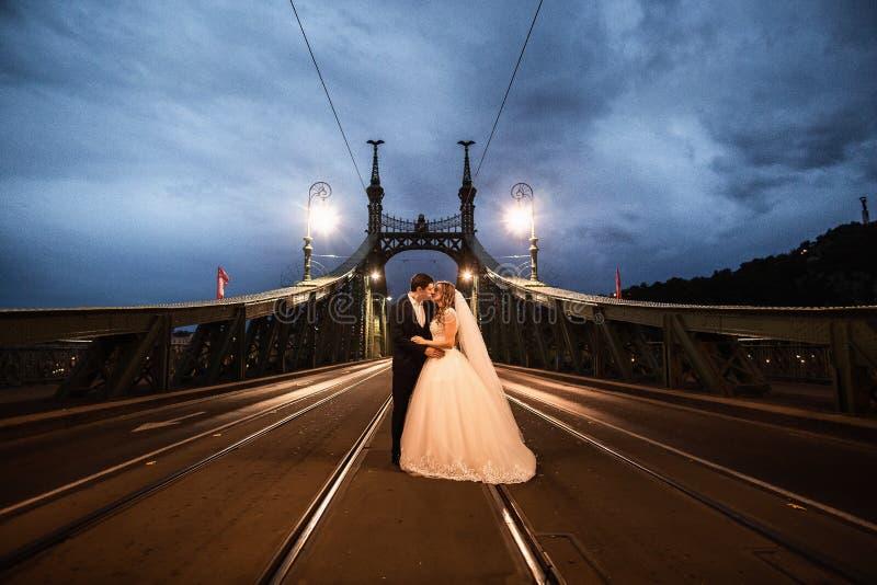 Jeunes belles paires élégantes de nouveaux mariés sur un pont à Budapest image stock
