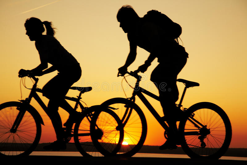 Jeunes bicyclettes d'équitation de couples au coucher du soleil photos libres de droits