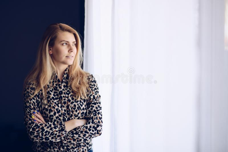 Jeunes blonds de femme par la fenêtre image libre de droits