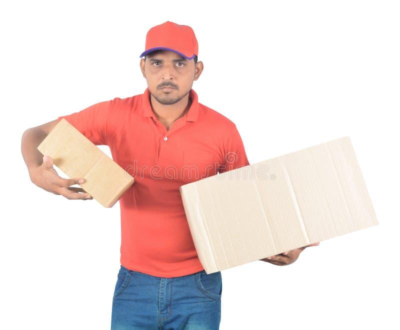 Jeunes boîtes de transport de carton de livreur dans l'uniforme photographie stock