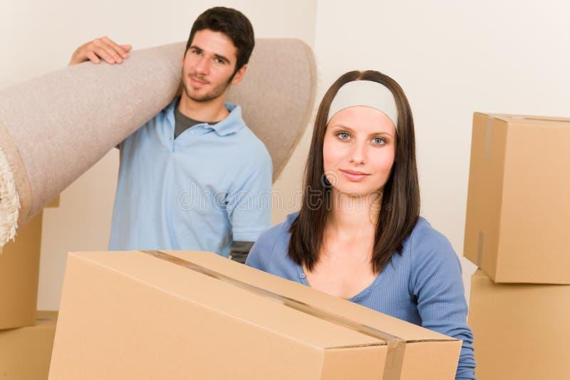 Jeunes cadres et tapis mobiles à la maison de couples images stock
