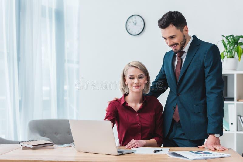 jeunes collègues de sourire d'affaires regardant l'ordinateur portable tout en travaillant ensemble photo stock