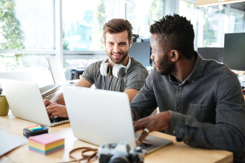 Jeunes collègues de sourire s'asseyant dans le bureau coworking utilisant l'ordinateur portable photo libre de droits