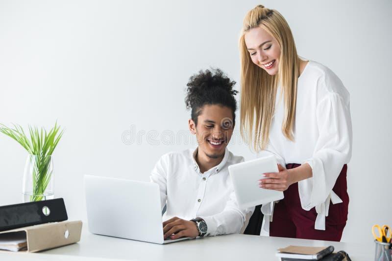 jeunes collègues multi-ethniques heureux d'affaires travaillant avec les dispositifs numériques photographie stock