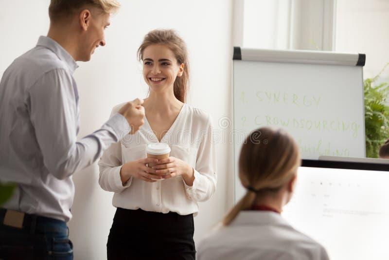 Jeunes collègues parlant riant de la pause-café dans coworking o photographie stock
