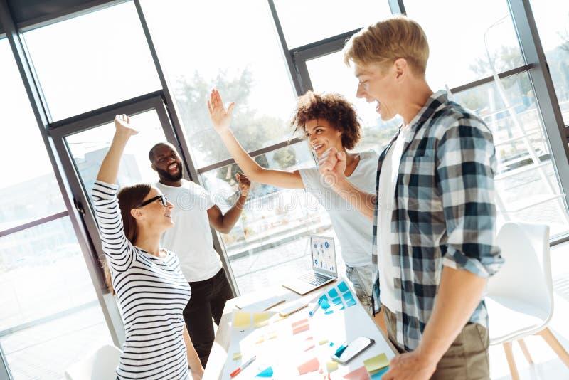 Jeunes collègues positifs se sentant heureux après leur projet réussi images stock