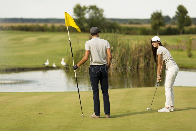 Jeunes couples à la cour de golf image libre de droits