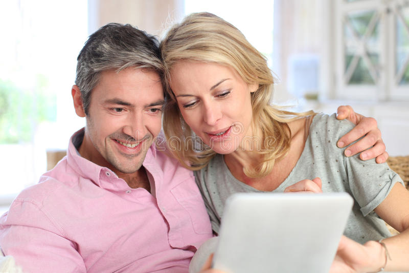 Jeunes couples à la maison appréciant à l'aide du comprimé photo libre de droits