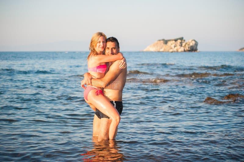 Jeunes couples à la plage images stock