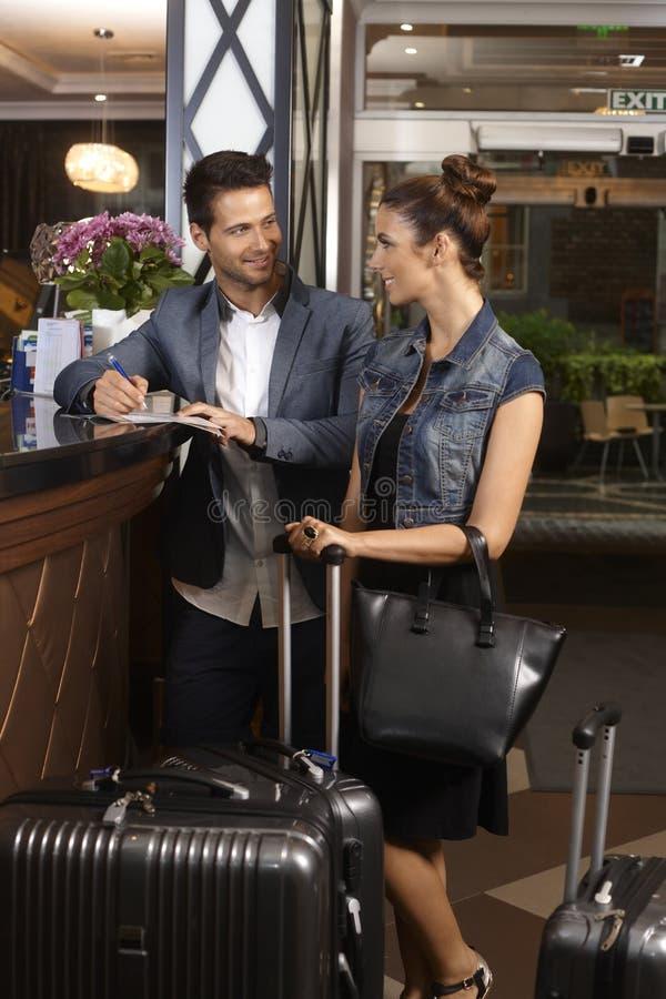 Jeunes couples à la réception d'hôtel photographie stock libre de droits