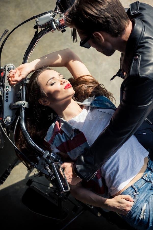 Jeunes couples élégants dans l'amour passant le temps ensemble sur la moto photos libres de droits