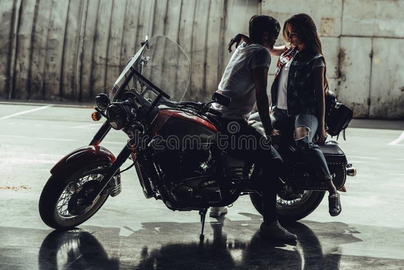 Jeunes couples élégants se reposant sur la moto et regardant l'un l'autre images libres de droits