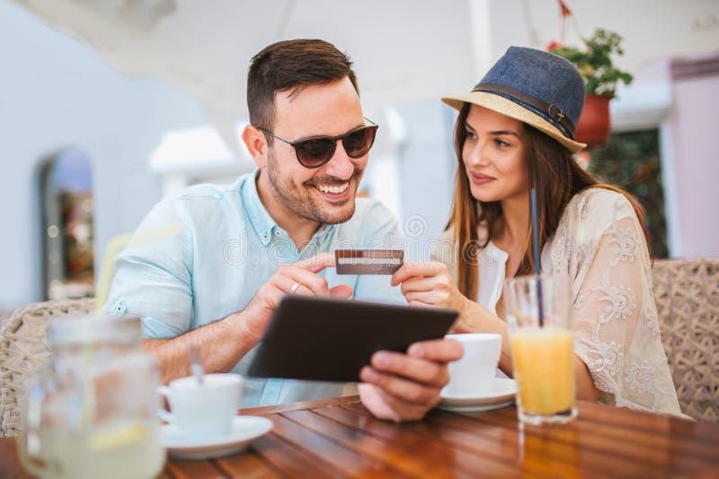 Jeunes couples étonnés faisant des achats en ligne par le comprimé numérique image libre de droits