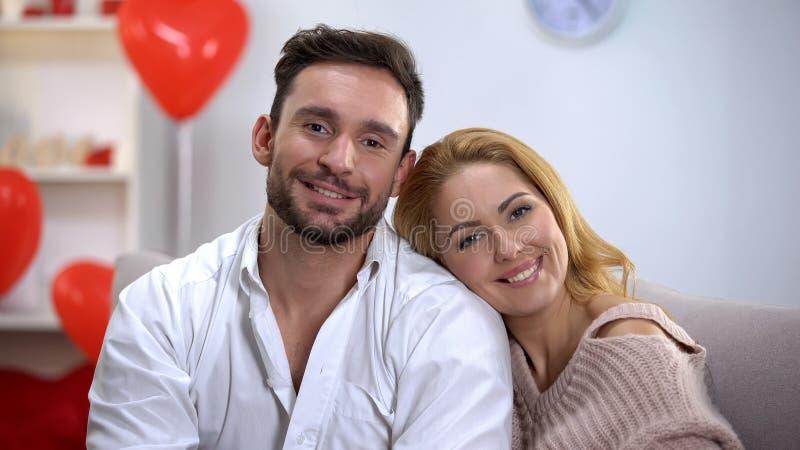 Jeunes couples étreignant et regardant dans la caméra, célébrant le jour de valentines à la maison photos stock